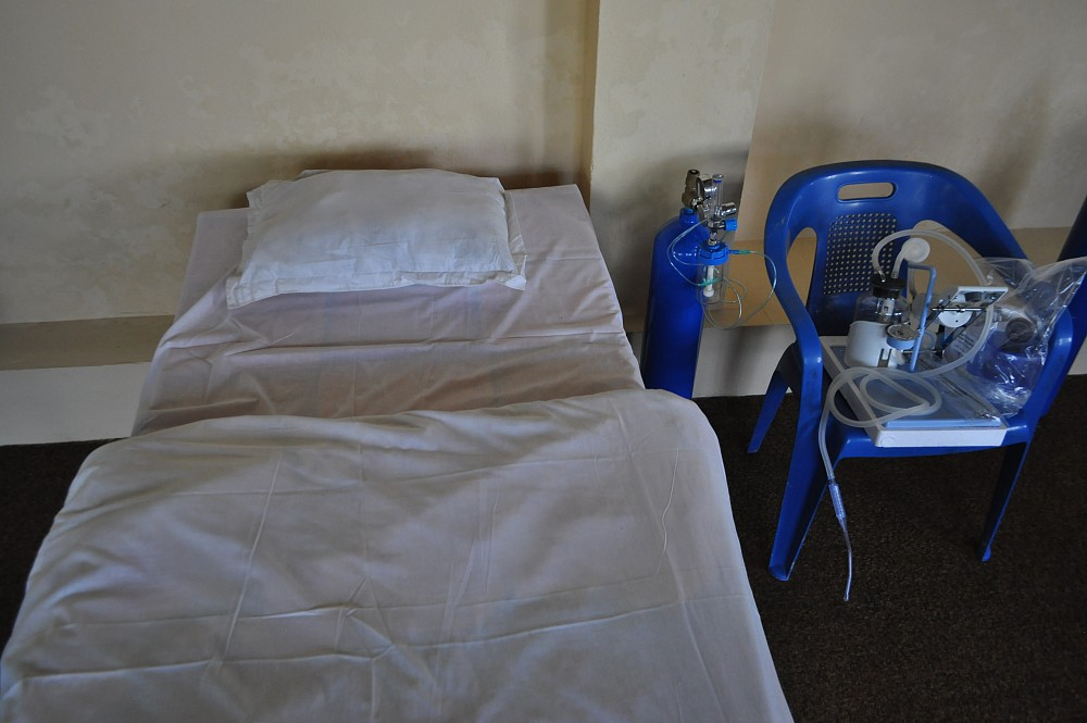 A hospital bed and a medical respirator.