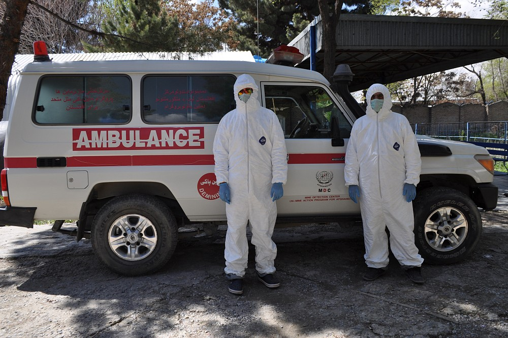 MDC Polyclinic staff in protective suits in front of the Polyclinic ambulance vehicle.
